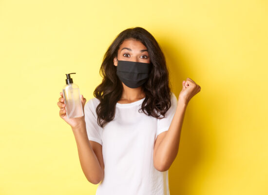 concept-of-covid-19-social-distancing-and-lifestyle-image-of-happy-african-american-woman-in-face-mask-feeling-happy-about-founding-good-hand-sanitizer-rejoicing-over-yellow-background